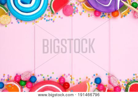 Double Border Of Assorted Colorful Candies Against A Pink Wood Background