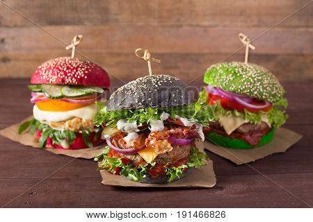 Black, green, red burgers on nice wood background