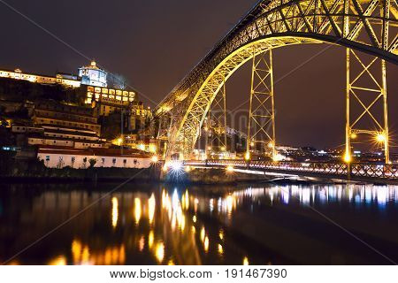 Dom Luis I or Luiz I iron arch bridge across Douro river with reflection and Monastery of Serra of Pilar in Porto at night, Portugal.