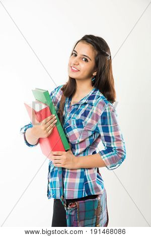 Good looking Indian female college student standing with bag holding books with or without spectacles, isolated over white background