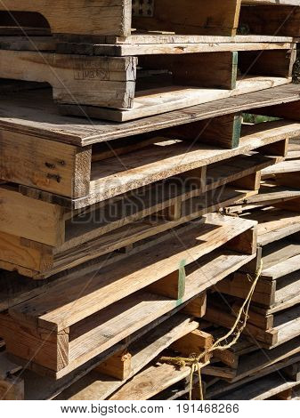 Uneven stacks of wooden pallets after they've been emptied.