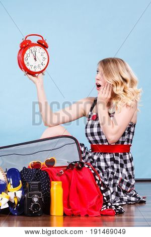Time for travel being late concept. Terryfied woman sitting on floor with messy packed suitcase holding big red old clock