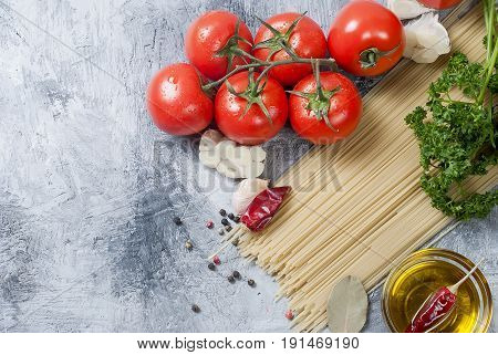 Ripe cherry tomatoes on a branch spaghetti linseed oil curly parsley garlic and spices on a concrete background. Top view Copy space.