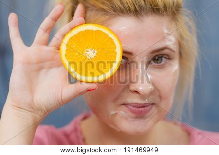 Woman Having Gel Mask On Face Holding Orange