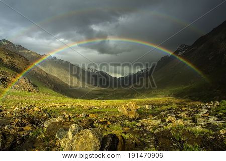 Double bright rainbow after the rain to the high mountains of the valley: above the green fields is a beautiful bright rainbow arc a summer day the Himalayas.