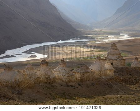 White ancient Buddhist stupa on the high bank above the mountain valley of the Zangla River sunset in Zanskar Himalayas India.