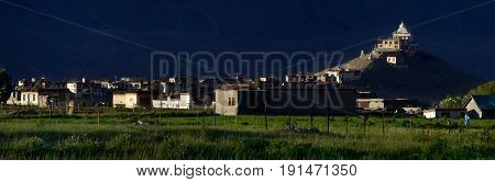 Huge Buddhist monastery at sunset: the outline of the gong building is lit by rays the backdrop is sunk in the shade bright green fields are planted in the valley of Tibet the Himalayas.