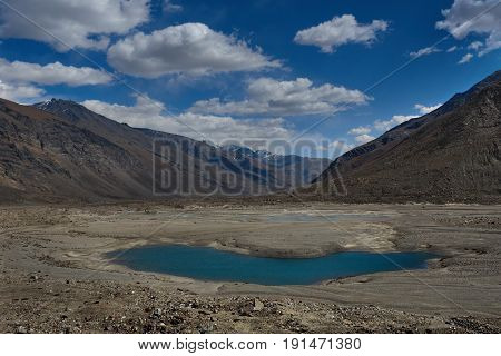 High mountains glacial lake oblong water body bright blue color water surface in the midst of a mountain valley with chains of brown peaks the Himalayas Tibet Northern India.