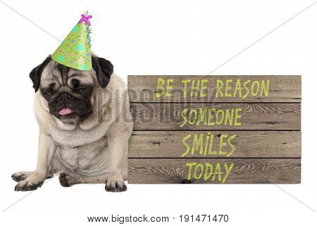 bad tempered pug puppy dog with wooden sign with text be the reason someone smiles today isolated on white background