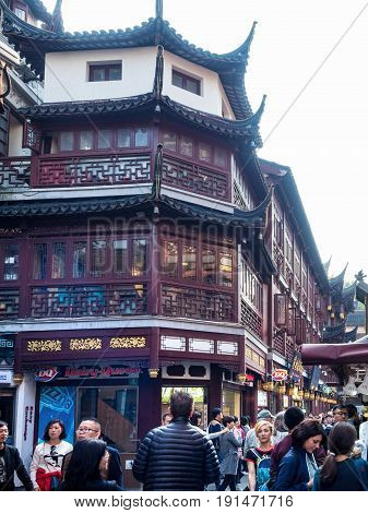 Shanghai, China - Nov 4, 2016: Around Yu Yuan (Yu Garden) - Old buildings with architectural structures in traditional Chinese styling converted to modern-day shops. Busy street scene.