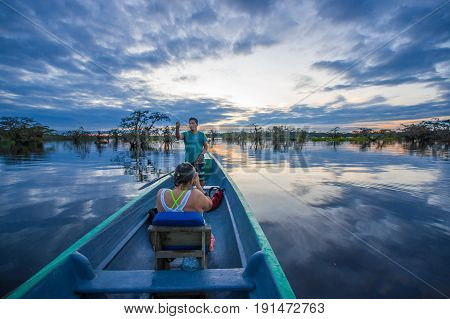 CUYABENO, ECUADOR - NOVEMBER 16, 2016: Unidentified people enjoying the sunset from the river in Cuyabeno National Park, Ecuador.