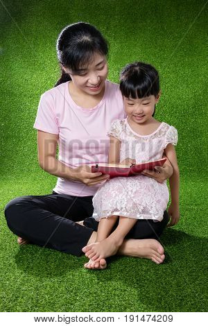 Asian Chinese Mother And Daughter Reading The Book