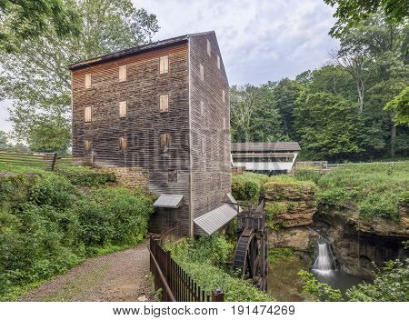 The restored historic Rock Mill grist mill stands beside a small white covered bridge crossing a beautiful gorge with a waterfall in Fairfield County Ohio.
