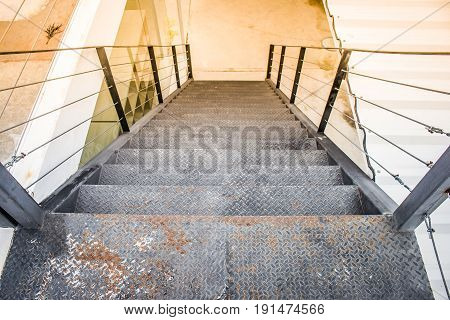 Top view close up a long metal stair outside buildings for exterior architecture. (Autumn filter effect)