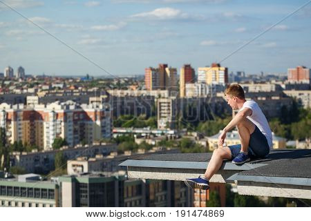 Roofer on the edge of the roof. A man looks at the city panorama from a high-rise building. Courage and adrenaline. Roofing
