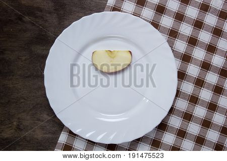 White plate with a slice of apple on a wooden table