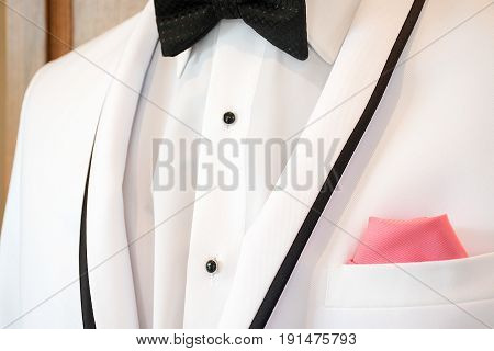 white tuxedo with black bow tie and pink handkerchief in pocket