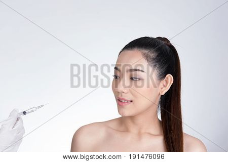 Doctor's hand making injection in girl's face. young asian woman receiving a hyaluronic acid injection. portrait against white background. Beauty treatment skin rejuvenation cosmetic procedure