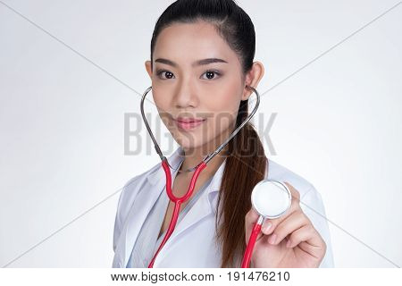 Female Doctor Showing Stethoscope For Checkup Over White Background. Physician Or Medical Practition