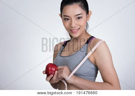 Sporty Fitness Woman With Measuring Tape And Red Apple Standing Against White Background. Diet, Spor