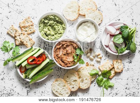 Vegetarian dip table. Eggplant harissa walnuts dip broccoli dip soft tofu and fresh vegetables on a light background top view. Flat lay
