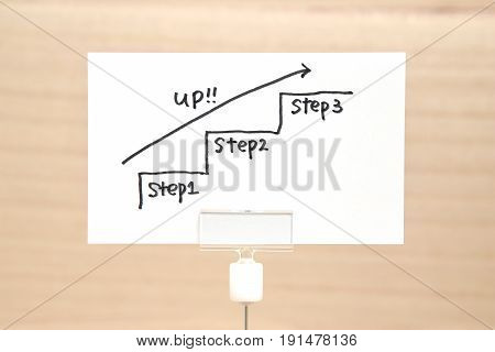 Hand writing stairs heading upwards with arrow on paper. Business success concept and growth idea.
