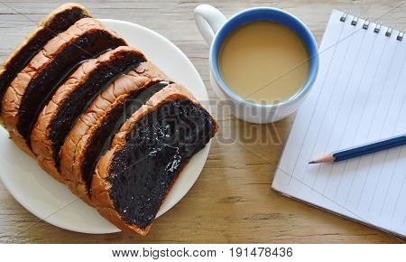 bread slice dressing creamy chocolate sauce and coffee with book