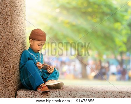 happy muslim kid with full dress playing smart phone asian traditional style dress