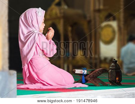 happy muslim girl with full hijab in pink dress asian traditional style dress praying inside the mosque and holy Allah