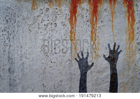 Zombie hands silhouette in shadow on concrete wall and blood background with copy space for text or image. Zombie and halloween theme with corpse hands on cemetery.