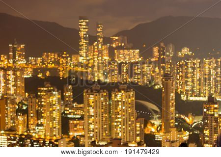 Hong Kong blurred bokeh light residence apartment building over high hill abstract background