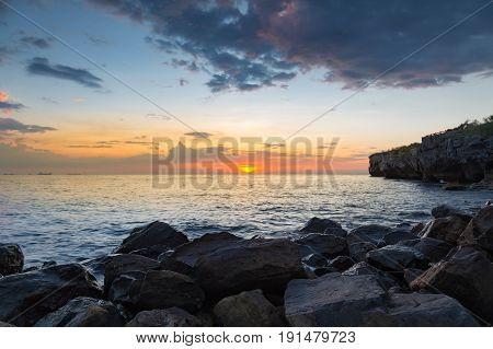 Rocky beach with sunset over seacoast skyline background nautral landscape backgorund