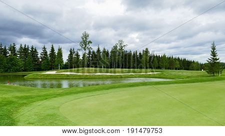 Green Golf Course in cloudy summer day