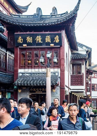 Shanghai, China - Nov 4, 2016: Around Yu Yuan (Yu Garden) - Old buildings with architectural structures in traditional Chinese styling converted to modern-day shops. Busy street scene. Focus on foreground pedestrians.