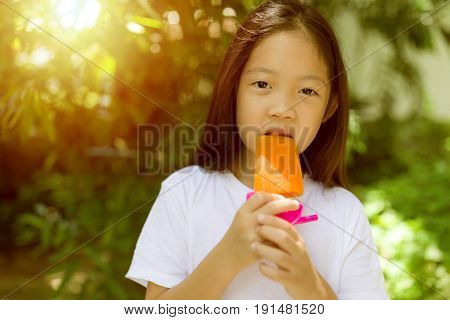 Happy Asian child eating popsicle ice cream during hot summer day.