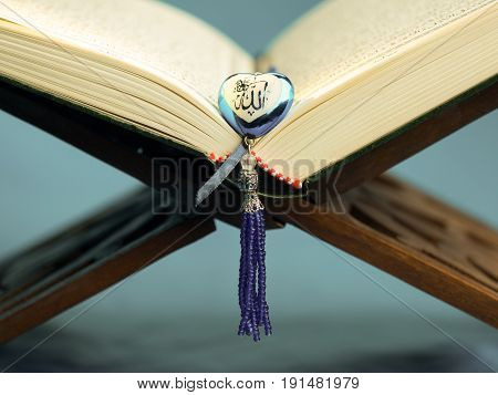 Islamic holy book Quran or Kuran in dark background with rosary in heart shape with arabic text