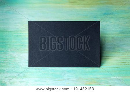 A photo of a blank black business card on a wooden teal blue texture. A mockup or a minimalist banner with copy space
