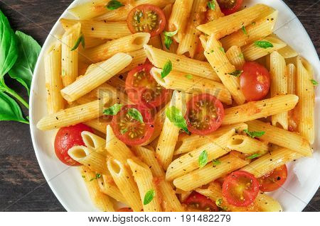 A closeup photo of a plate of pasta with tomato sauce. Penne rigate with cherry tomatoes and fresh basil leaves