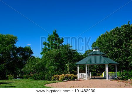 A White Gazebo with Green Roof and Red Brick Patio in a Park on a Sunny Day
