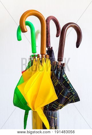 Umbrellas of different colors with handles close-up on a white background