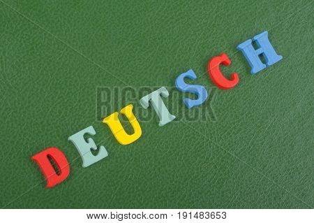 DEUTSCH word on green background composed from colorful abc alphabet block wooden letters, copy space for ad text. Learning english concept