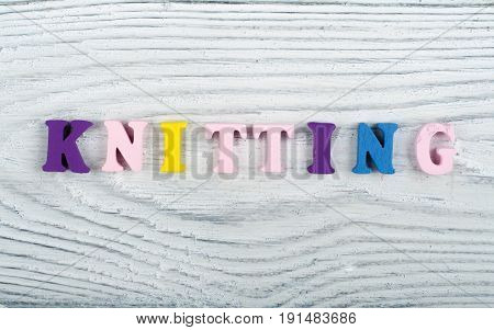 Knitting. Knitted Fabric Texture. Word composed from ABC alphabet letters on wooden background