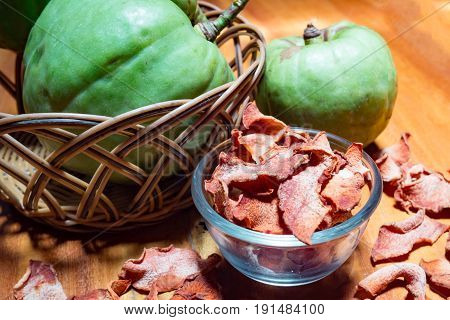 Dry garcinia in glass bowl with green Garcinia atroviridis fruit. Garcinia is healthy herb food that has high vitamin C and hydroxy citric acids (HCA) for diet.