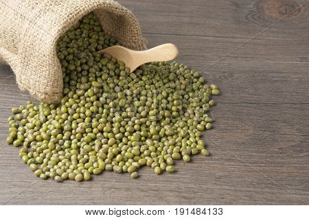 Mung Bean In Sack With Wooden Spoon On Wood Background