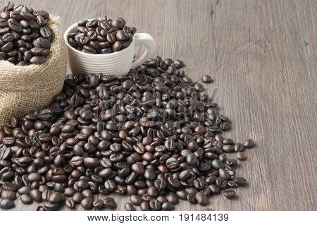 Stack Of Coffee Bean In White Cup And Brown Sack