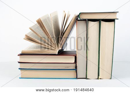 Open book, hardback colorful books on wooden table, white background. Back to school. Copy space for text. Education business concept