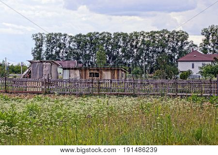 Barn, house and outbuildings in the yard behind a wooden fence near the green field
