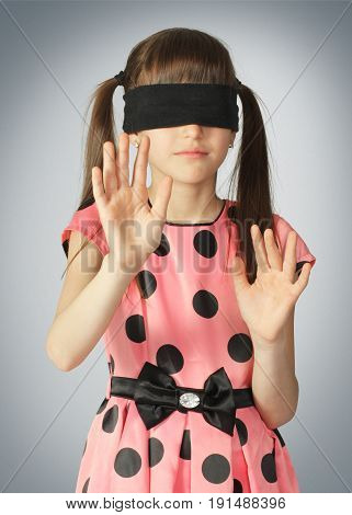 Child with blindfold blind concept on grey background