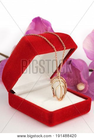 golden pendant in jewelry box with flower background