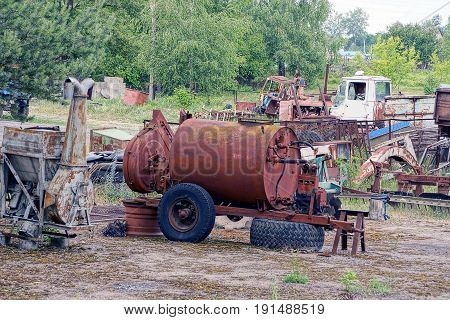 Rusty tank on wheels among old equipment and scrap metal
